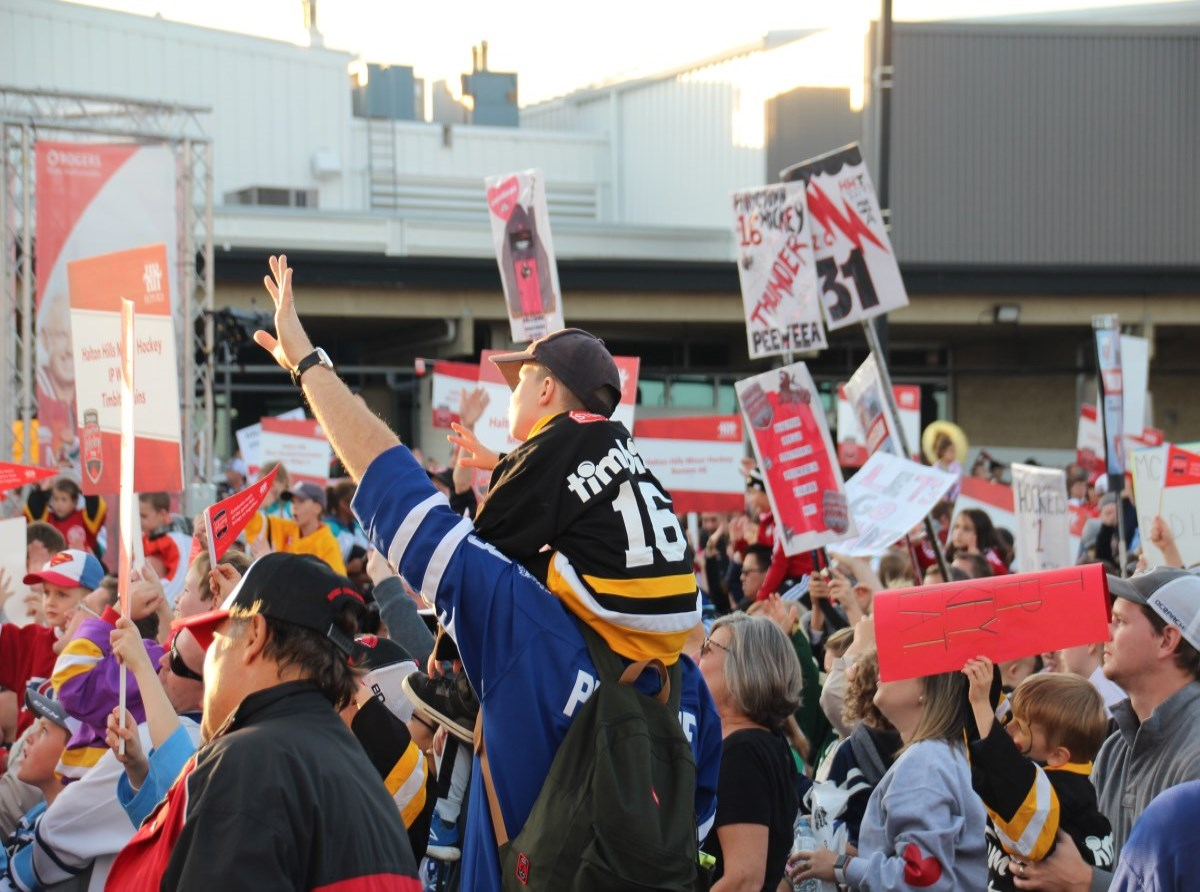 Crowd of cheering hockey fans in jerseys with kid on shoulders